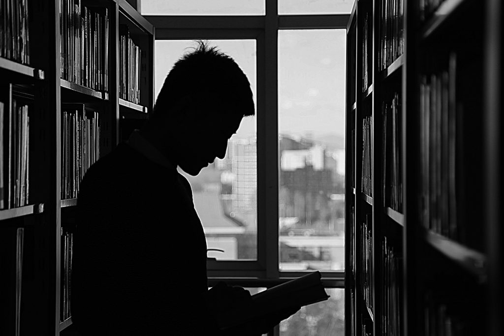 man standing in a library black and white
